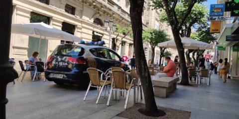 Rúa do Paseo. Terrazas y coche de la policía.