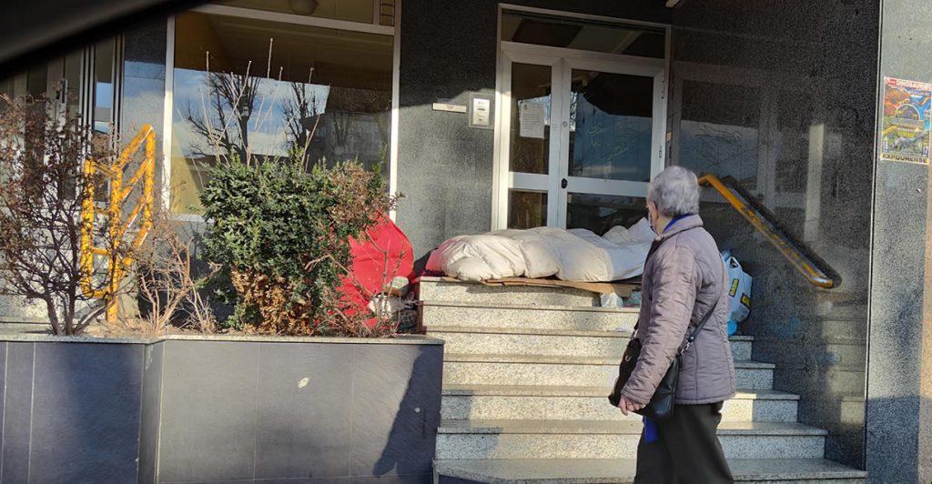 Persona sin techo durmiendo en la calle con señora mirando